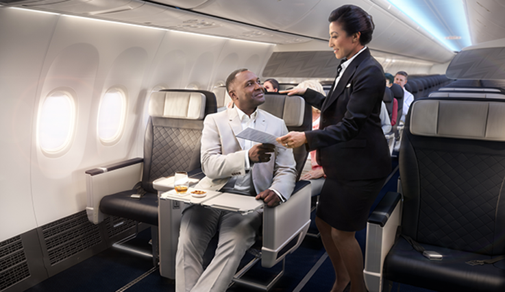 Cabin crew member serving a gentleman seated in Premium on a WestJet 737 Max.