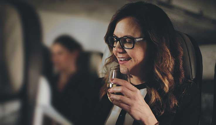 Woman enjoying glass of wine in upgraded Premium seat