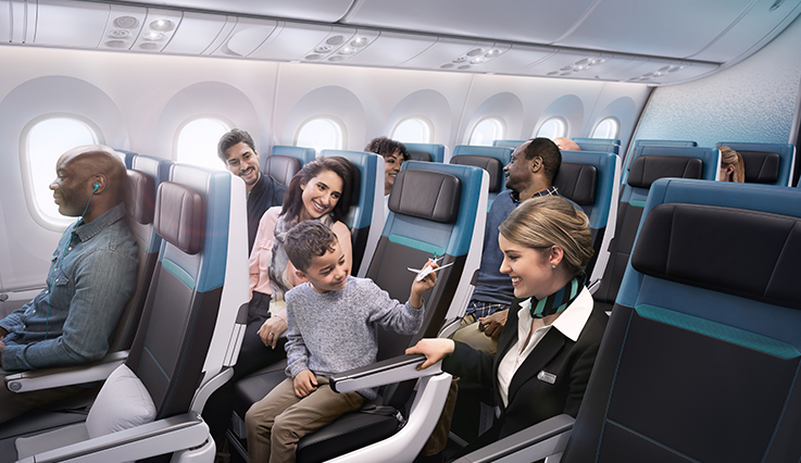 WestJet flight attendent in aisle positively interacting with seated child pretending to fly toy plane in Economy cabin