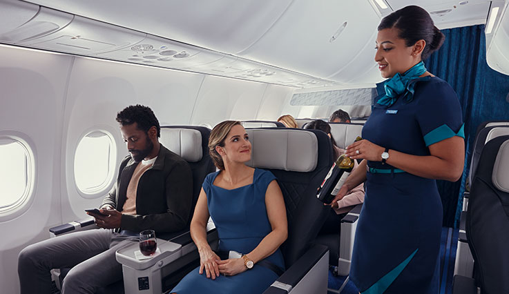 Cabin crew member presenting wine bottle to guest seated in a premium cabin.