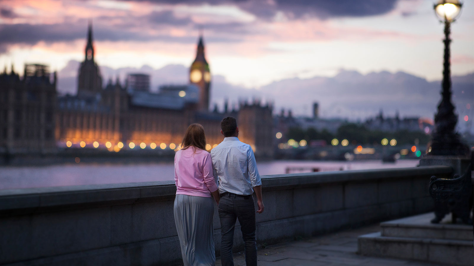Couple walking along the Thames in London.