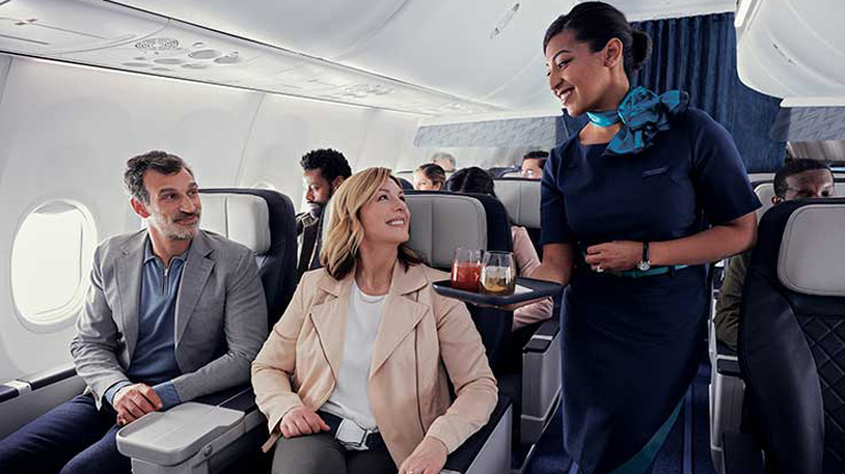 Premium cabin guests greeted by a WestJet flight attendant