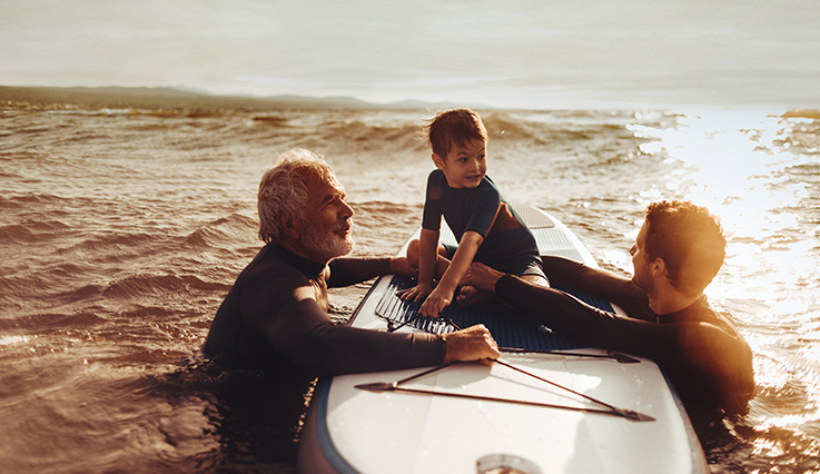 Grandfather, father and son swimming in the ocean.
