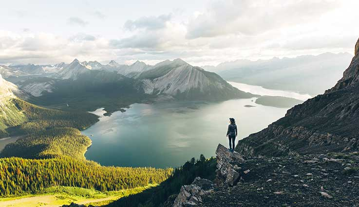 Hiker on mountain overlooking lake