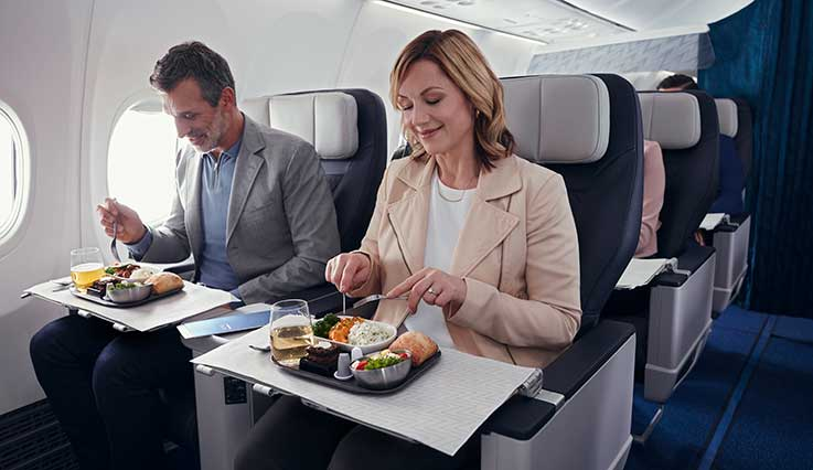 Guests enjoying food and beverages served in Premium cabin