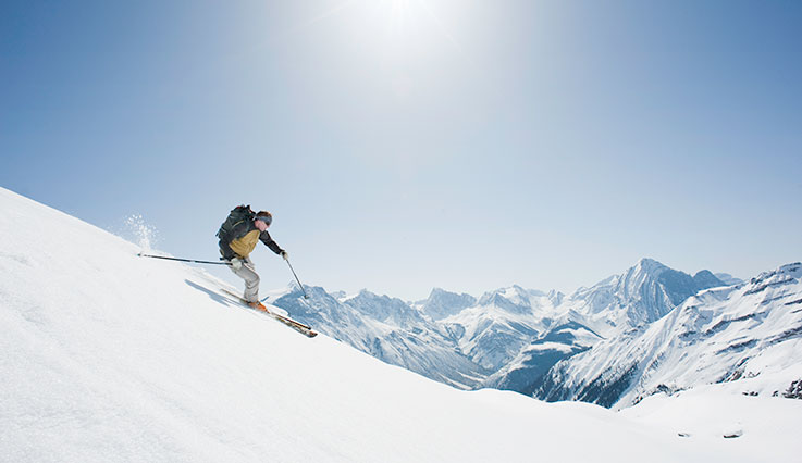 Downhill skier skiing in Canadian mountains