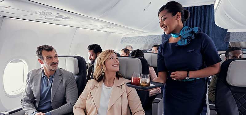 Couple seated in Premium cabin receiving drink service from Flight Attendant.