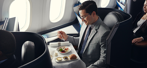 Businessman enjoying a meal in his luxurious Business cabin pod.