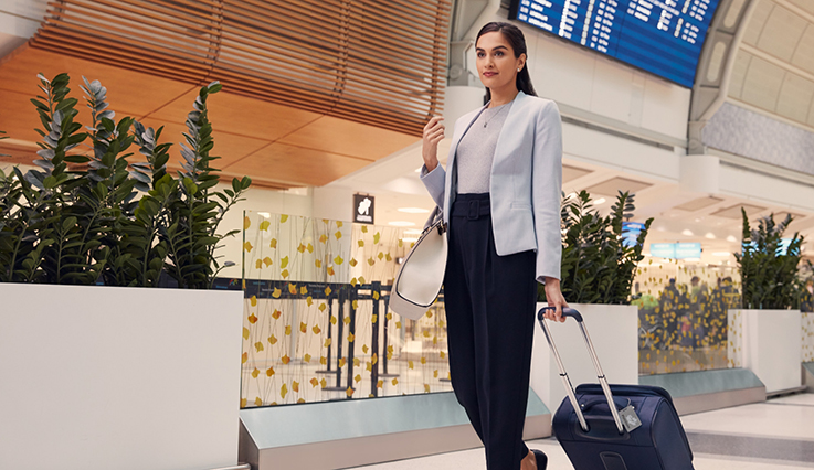Businesswoman walking in airport with suitcase
