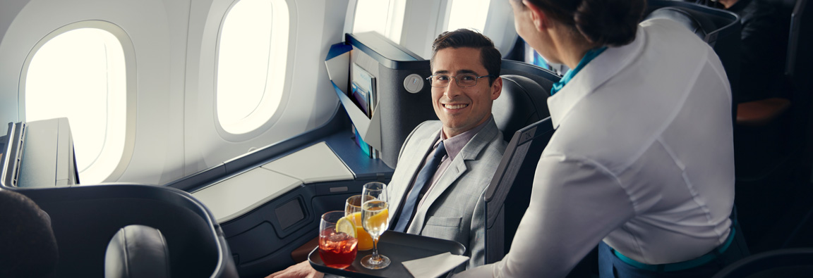 Cabin crew member serving a beverage to a guest seated in a Business cabin pod. Part of WestJet's dine anytime service on the 787 Dreamliner.
