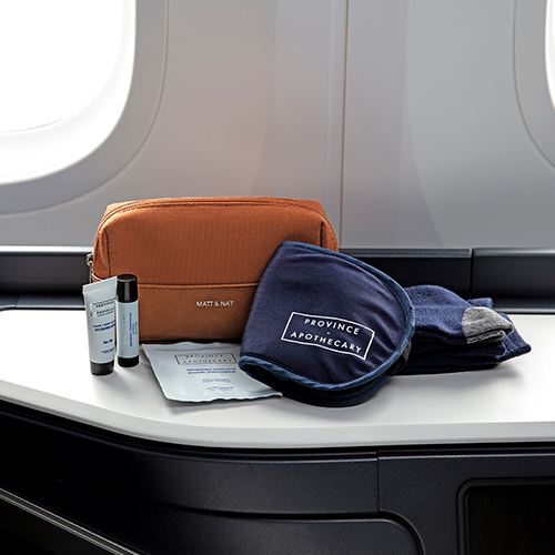Tan colored Matt and Nat amenity kit displaying a variety of nourishing Province Apothecary skincare products.