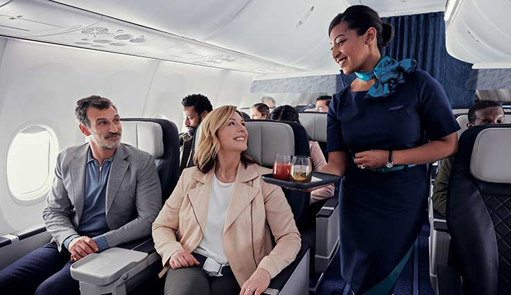 Couple being served beverages in the premium cabin