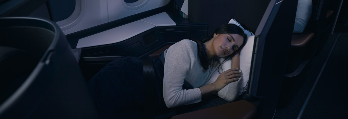 Guest relaxes in a lie-flat seat in their Business cabin pod on WestJet's Boeing 787 Dreamliner.