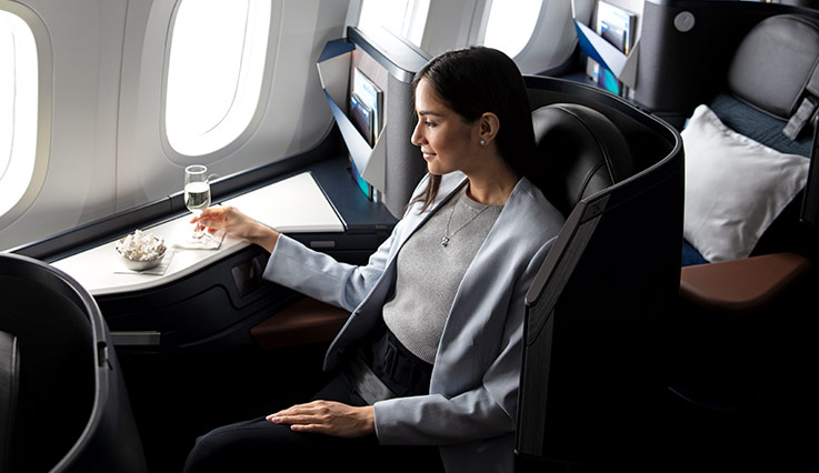 Woman enjoying a glass of sparkling wine in Business seat