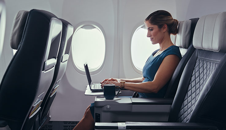 Frequent traveller working on laptop in Premium seat