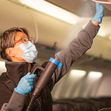 WestJetter cleaning the overhead bin by fogging