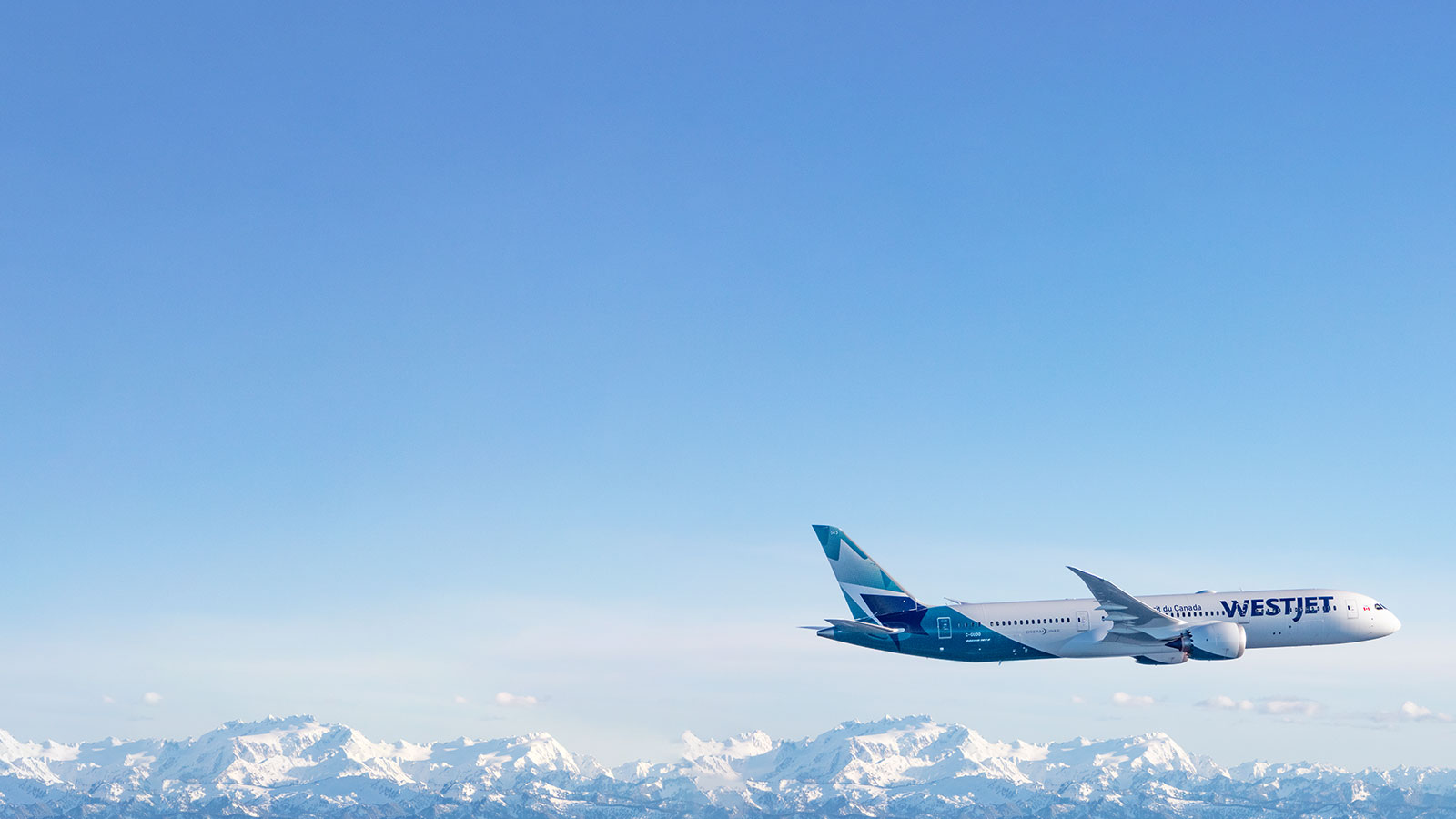 WestJet aircraft flying over the mountains.