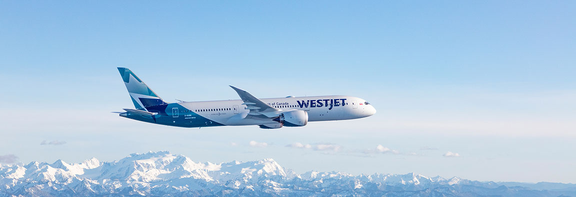 WestJet aircraft flying over mountains
