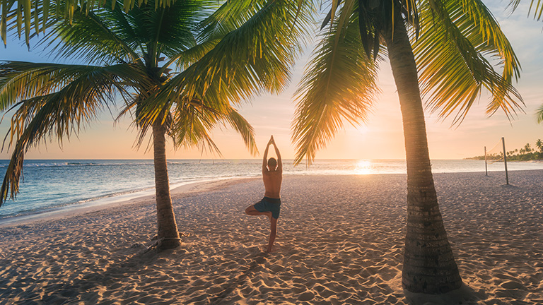 Man doing yoga on a tropical beach