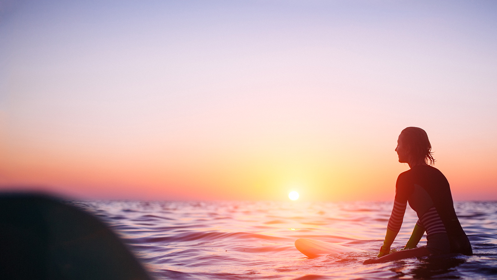 Surfer looks at a sunset from the water.