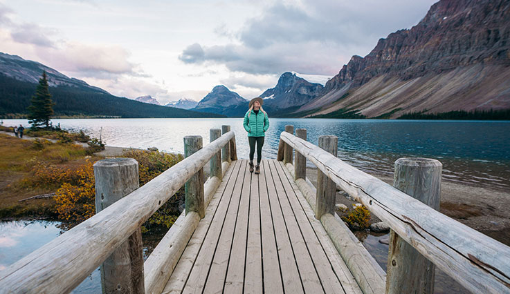 Visitor standing on bridge with view of lake in the Rocky Mountains