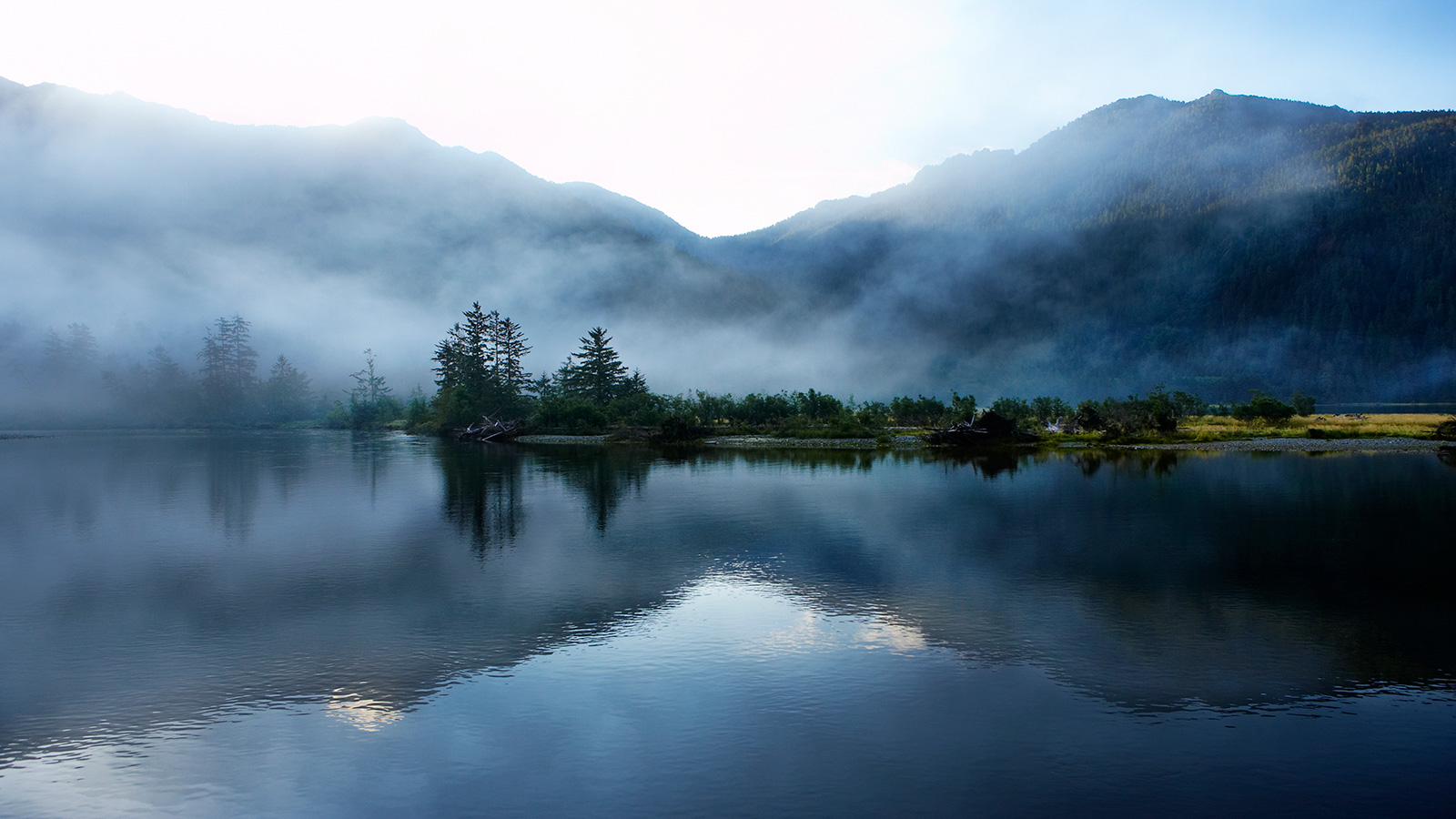 Spooky fog settles over a mountain lake