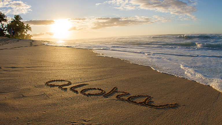 Aloha written in the sand at sunset.