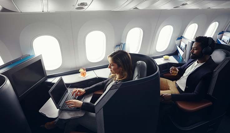 Guest working on laptop in Business pod onboard the Dreamliner