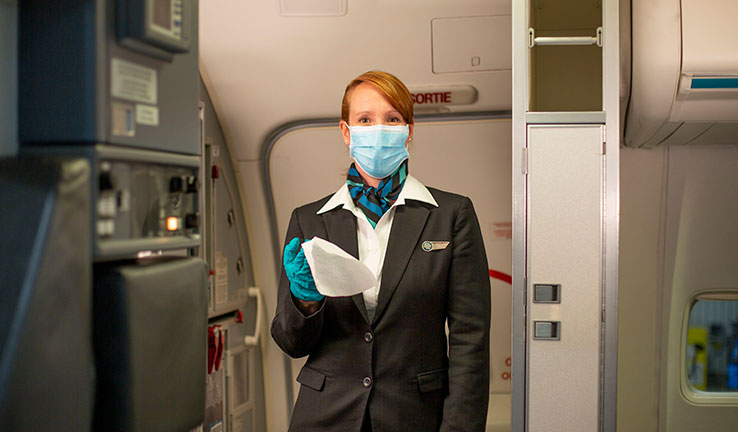 WestJet crew wearing mask and gloves and offering a disinfectant wipe upon boarding
