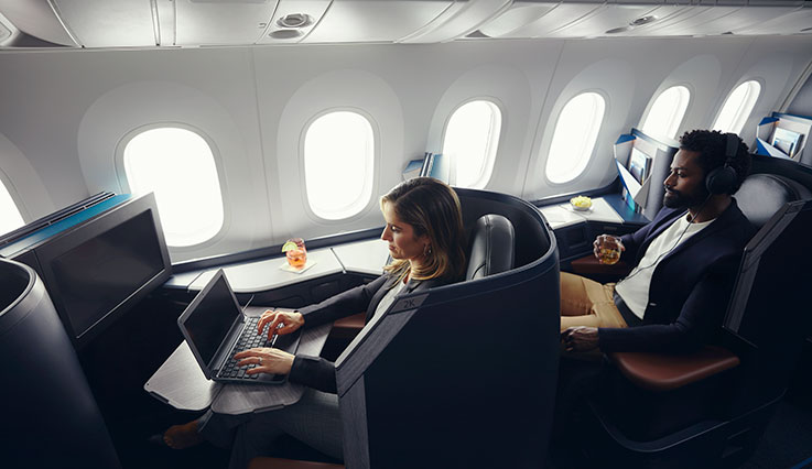 Guests relaxing in Business pods onboard the Dreamliner