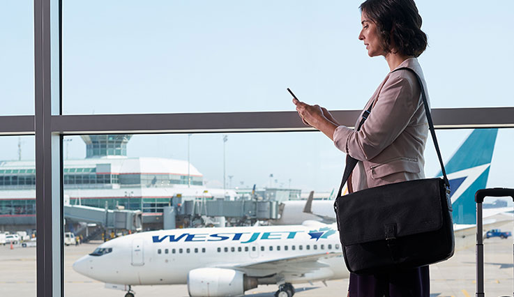 Woman travelling for business at the airport walking past WestJet plane beyond the window