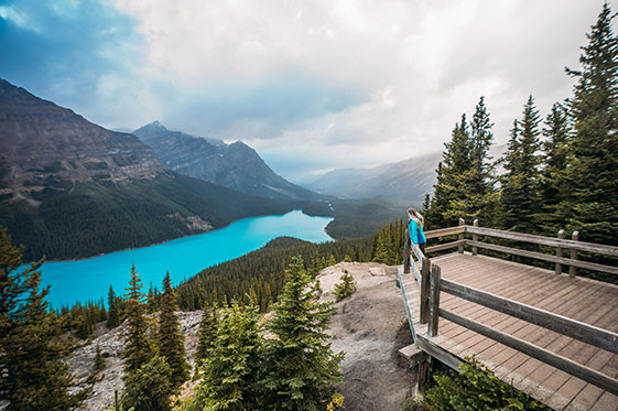Visitor in Rocky Mountains overlooking lake