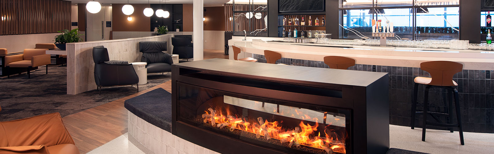 A rounded fireplace in front of the bright rounded bar