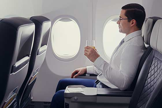 Business traveller enjoying a drink while seated in Premium cabin