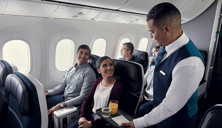Flight attendant serving guests seated in Premium