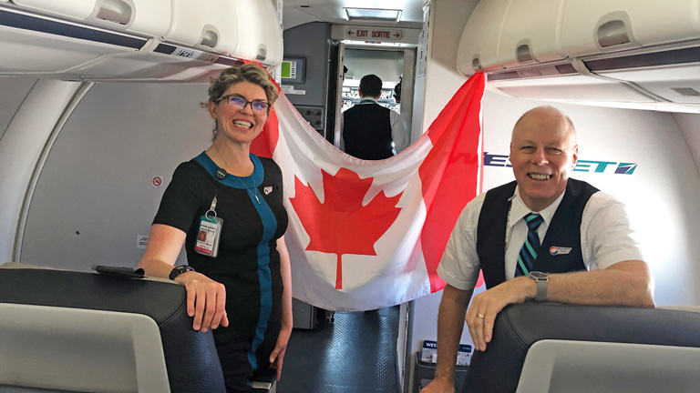 Man and woman flight attendants with Canadian flag behind them