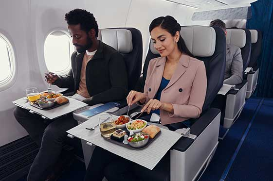Professionals enjoying onboard meal while seated in Premium cabin