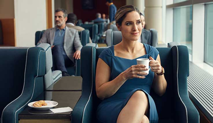 Business professional drinking coffee in airport lounge