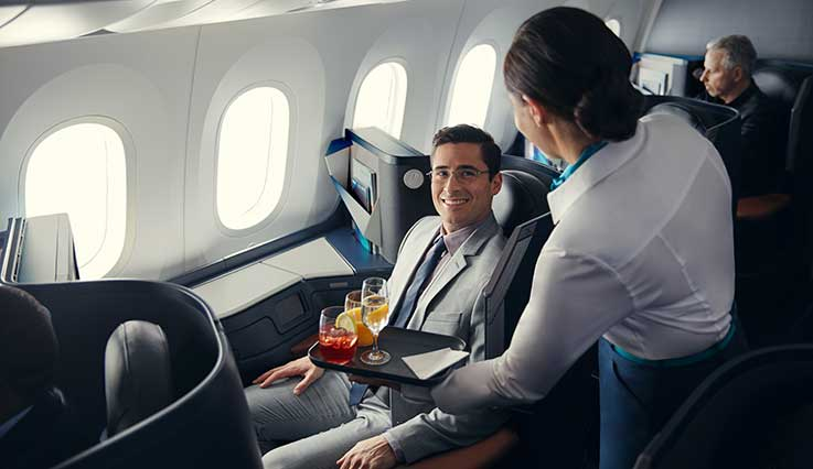 Cabin crew member serving drink to guest seated in Business cabin of WestJet Boeing 787 Dreamliner