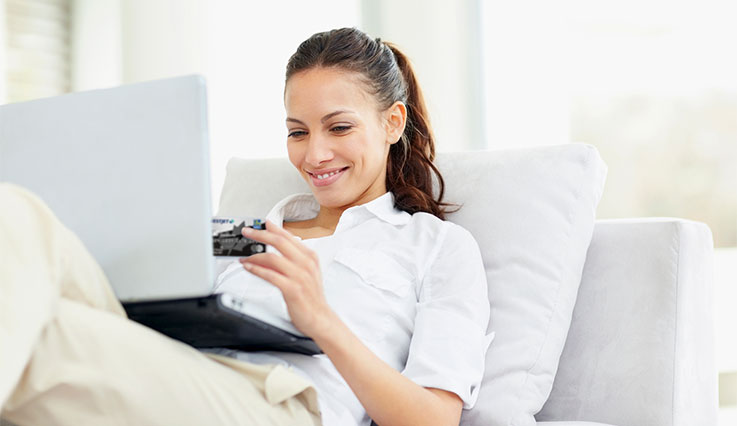 woman sitting on couch online shopping with her WestJet RBC World Elite Mastercard