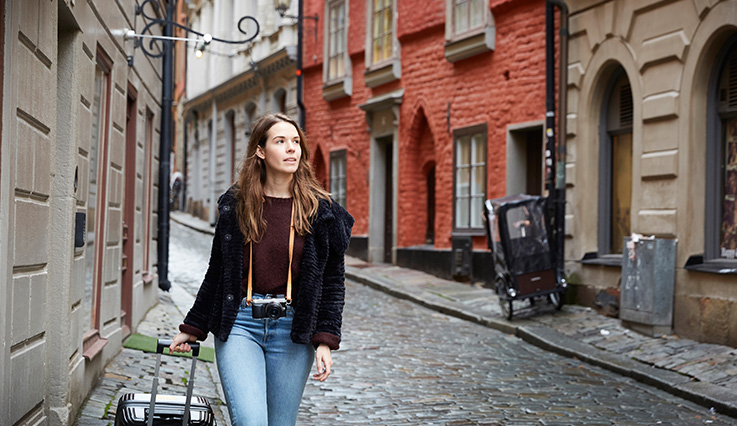 Woman on European cobblestone street with rolly luggage for flights bought on Boxing day