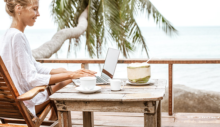 woman sitting on the beach leaning on palm tree with laptop