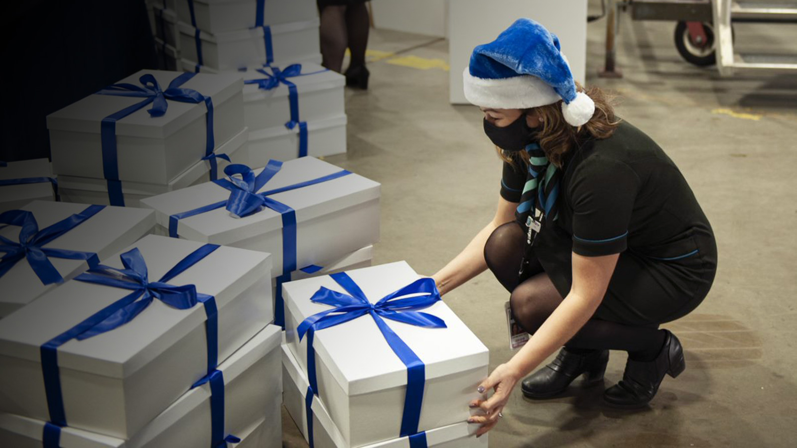 Masked WestJetter in a blue Santa hat smiles in front of a hangar full of boxes.