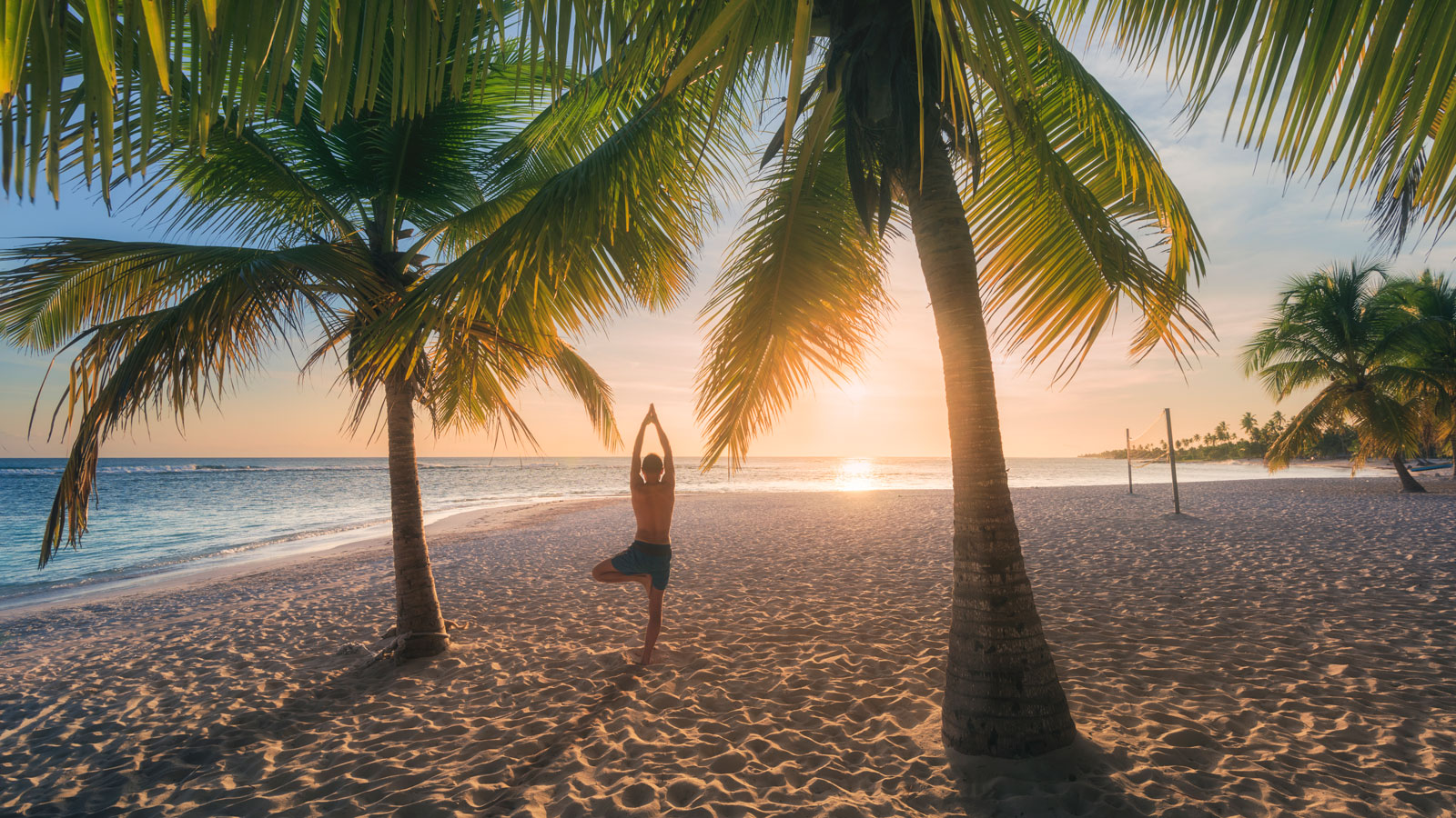 young man doing yoga on beach at sunset
