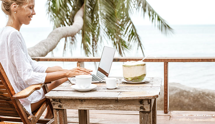 Woman in a tropical setting working on laptop