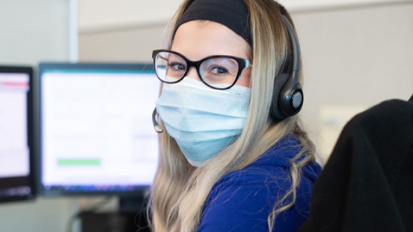 A WestJet call centre agent with facemask helping guests on the phone.
