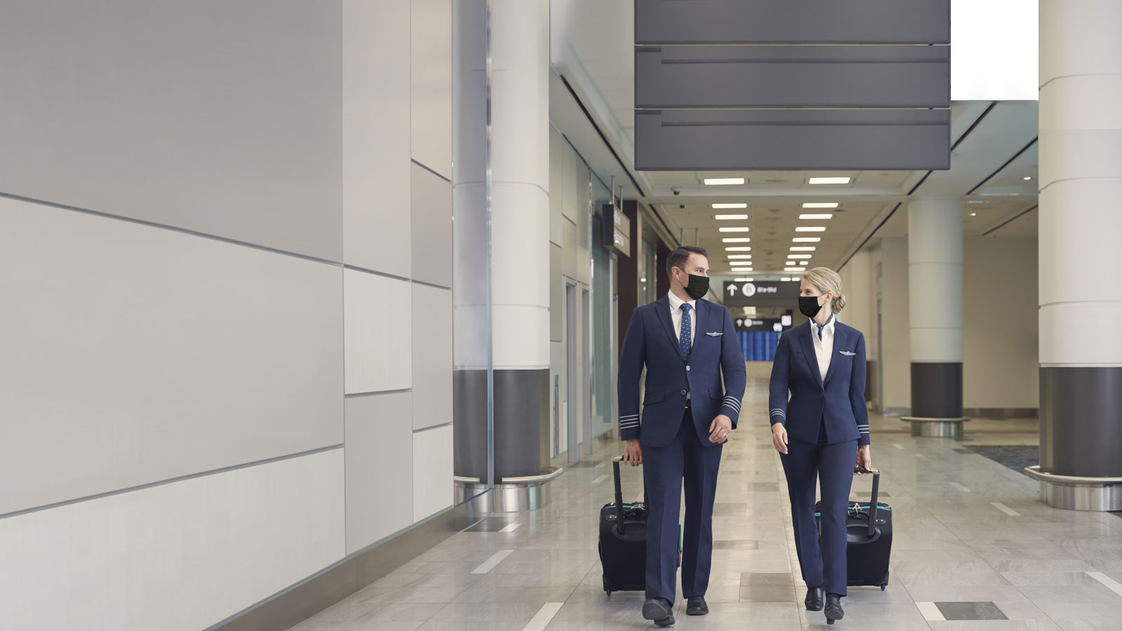 Masked pilots walking through airport.