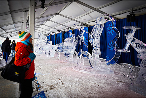 Showing slide 6 of 21 in image gallery, Woman admiring the ice scultures at Winterlude in Ottawa