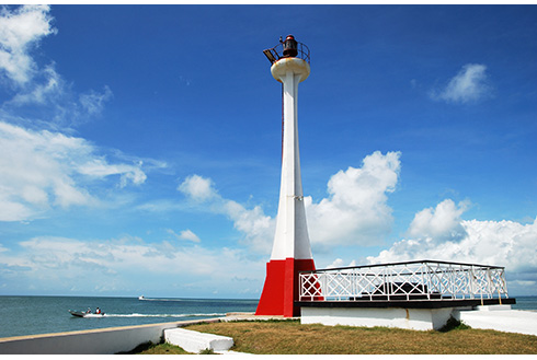 Showing slide 4 of 8 in image gallery, Red and white lighthouse with boats passing by in Belize City