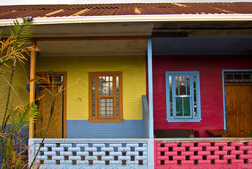 Showing slide 5 of 10 in image gallery, The outside of two San Jose homes that are painted bright colours
